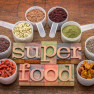 superfood abstract (wheatgrass, acai berry, goji berry, falx seed,chia seed,goldenberry,hemp seed, quinoa grain) - a set of measuring scoops with la letterpress text against rustic wood